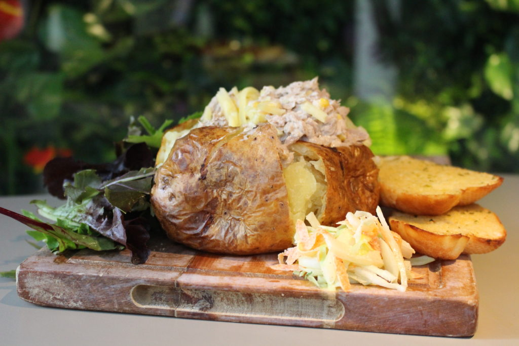 Baked potato with tuna and garlic bread on a wooden board