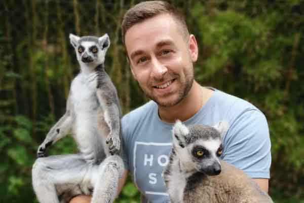 Man with lemurs sat on arms