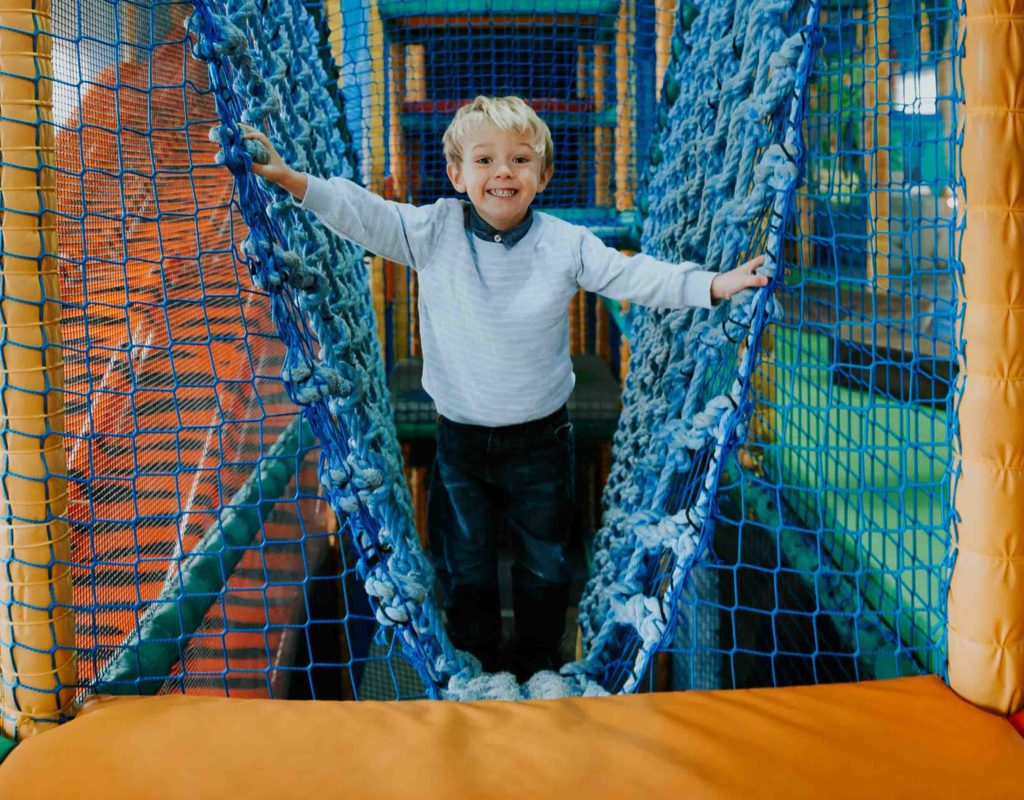 Child climbing on netting in play area