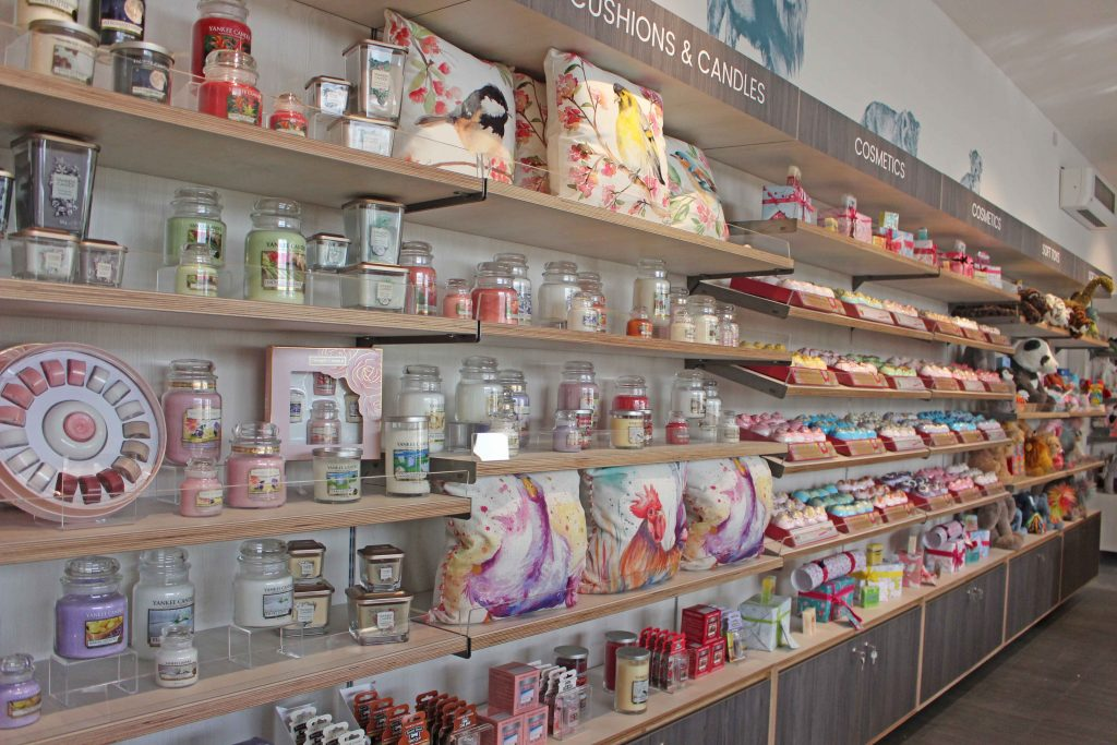 Shelves in gift shop displaying cushions and candles