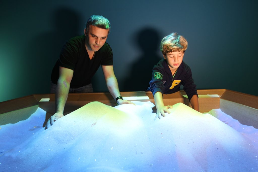 Adult and child playing with interactive sand pit.