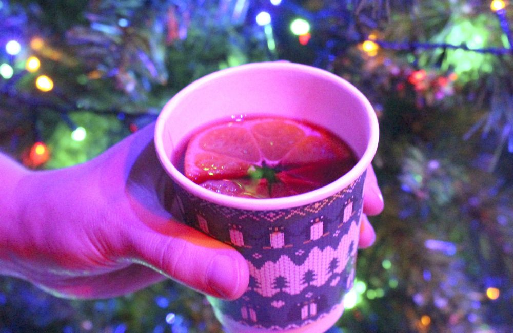 Cup of mulled wine with Christmas tree lights in the background