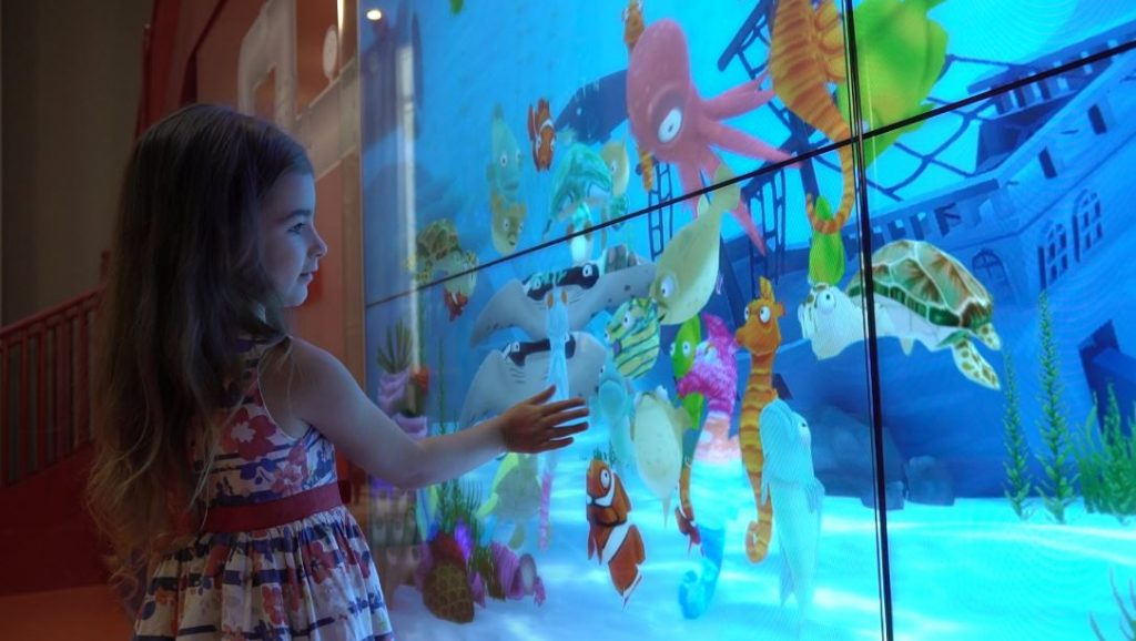 Young girl playing with interactive characters on a screen